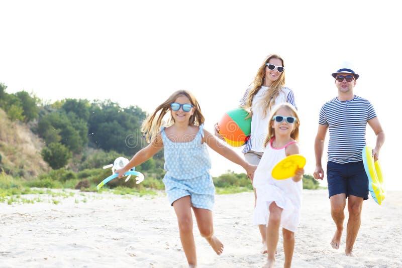 Família com as crianças que correm na praia imagens de stock