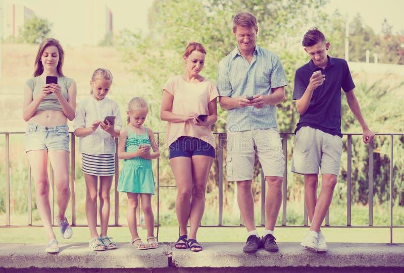 Família com as crianças que jogam com telefones celulares foto de stock