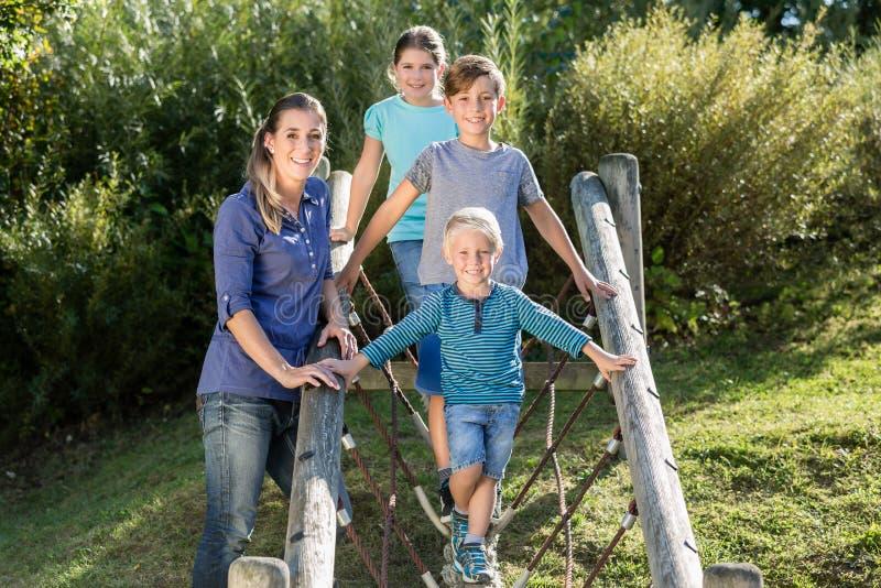 Família com as crianças que jogam no campo de jogos da aventura fotografia de stock royalty free