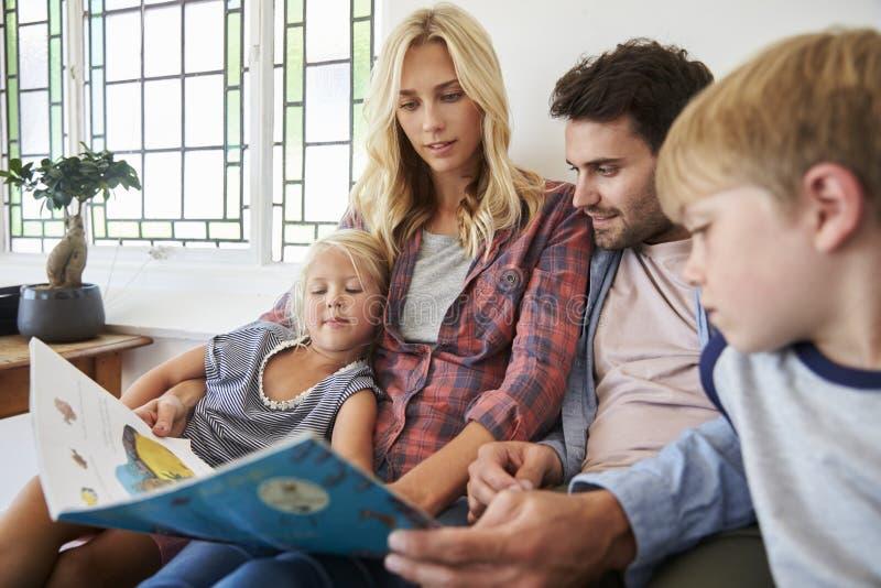 Família com as crianças que sentam-se no livro de leitura da cama junto imagem de stock royalty free