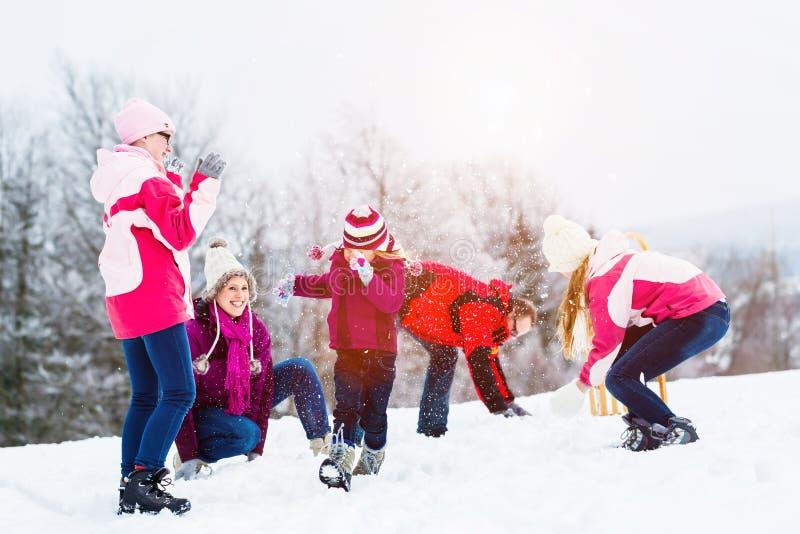 Família com as crianças que têm a luta da bola de neve no inverno foto de stock royalty free