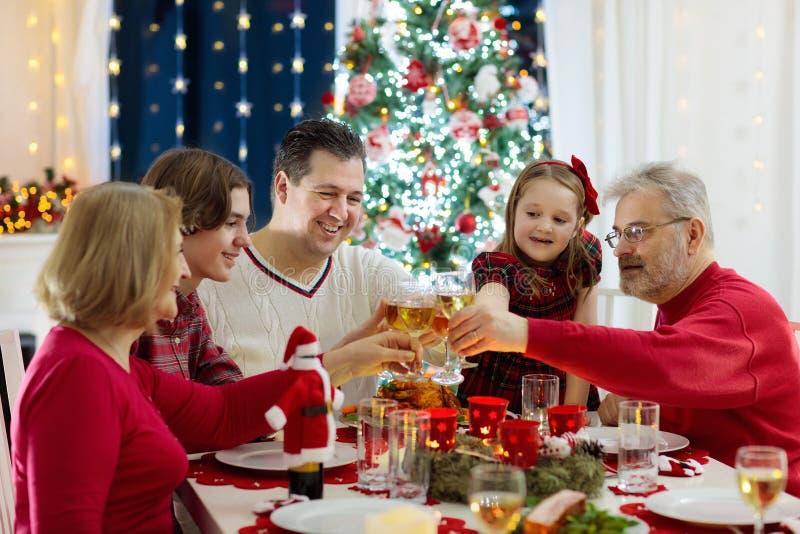 Família com as crianças que têm o jantar de Natal na árvore fotografia de stock royalty free