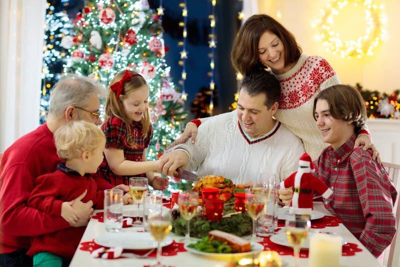 Família com as crianças que têm o jantar de Natal na árvore fotos de stock
