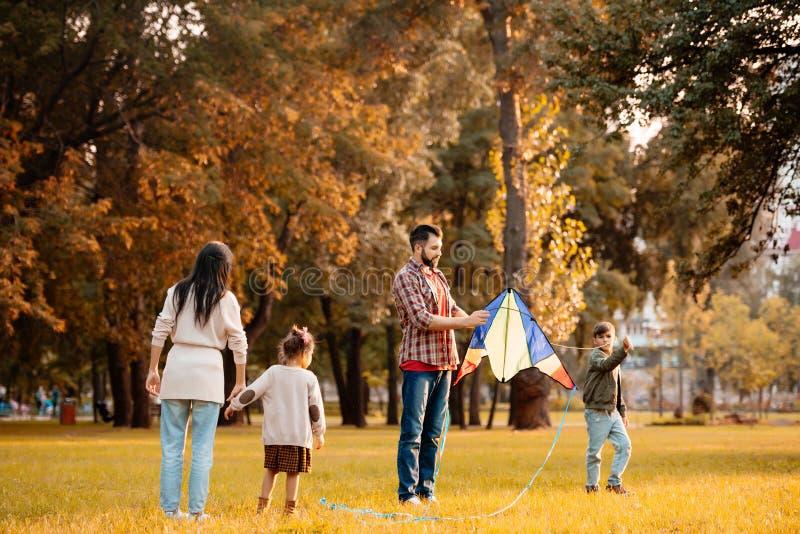 Família com as crianças que tentam voar um papagaio no imagem de stock royalty free