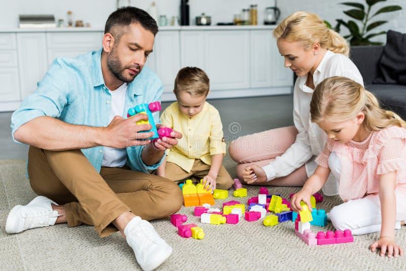 família com as duas crianças pequenas que sentam-se no tapete e que jogam com colorido foto de stock