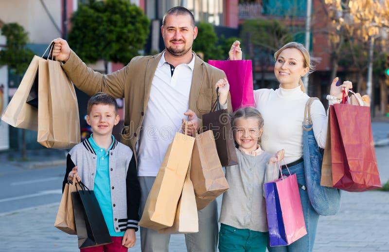 Família com as duas crianças que guardam sacos de compras imagens de stock
