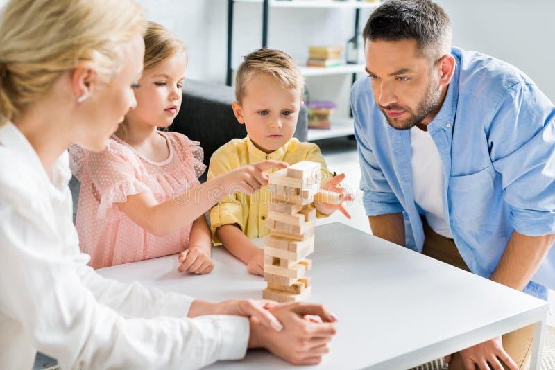 família com as duas crianças que jogam com blocos de madeira imagens de stock