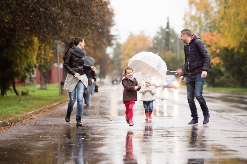 Família com as filhas sob os guarda-chuvas, correndo Dia chuvoso fotos de stock royalty free