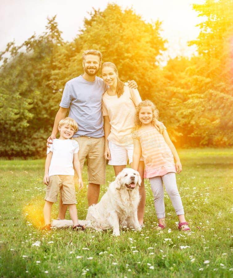 Família com cão e crianças imagem de stock