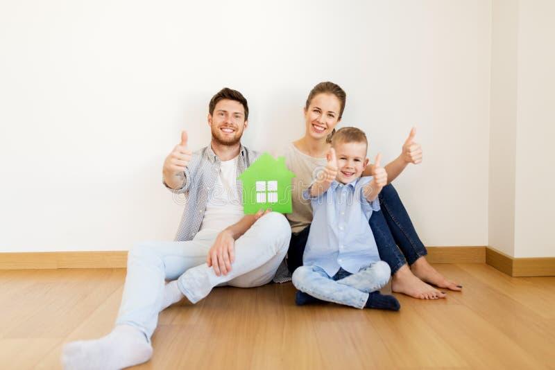 Família com a casa verde que mostra os polegares acima em casa foto de stock royalty free