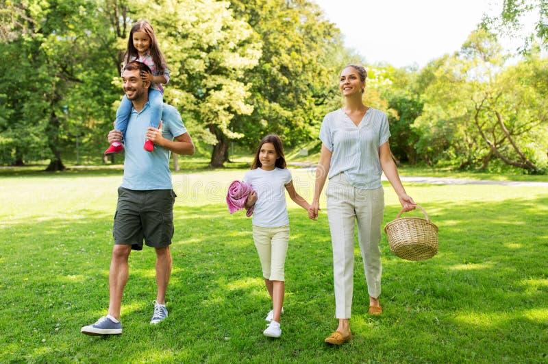 Família com cesta do piquenique que anda no parque do verão imagem de stock royalty free