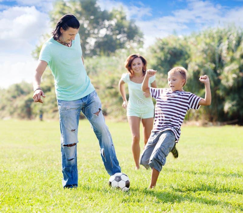Família com a criança do adolescente que joga com bola de futebol imagens de stock