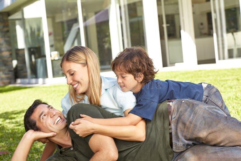 Família com a criança no jardim da casa fotos de stock royalty free