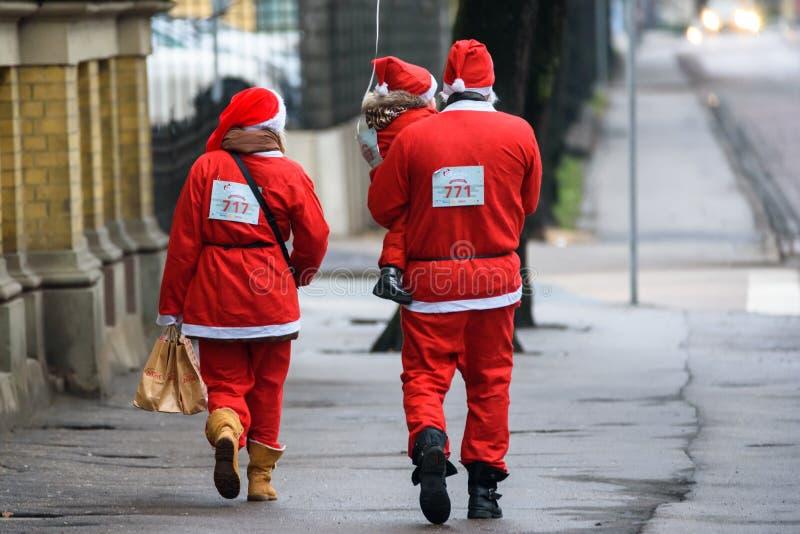 Família com criança pequena, após a corrida do divertimento de Santa em Riga fotografia de stock