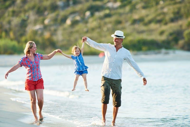Família com a criança pequena na praia do mar imagem de stock royalty free