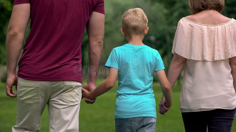 Família com a criança que guarda as mãos, andando afastado, a unidade e o apoio da família imagens de stock