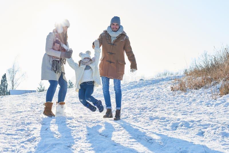 Família com a criança que joga na neve foto de stock royalty free