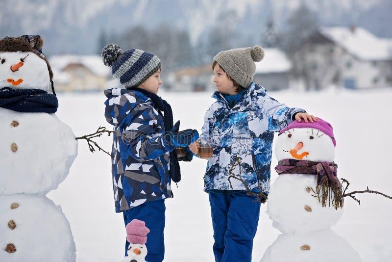 Família com crianças, boneco de neve de construção no parque em pouco vil foto de stock