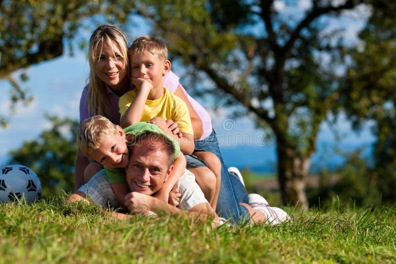 Família com crianças e futebol em um prado fotos de stock