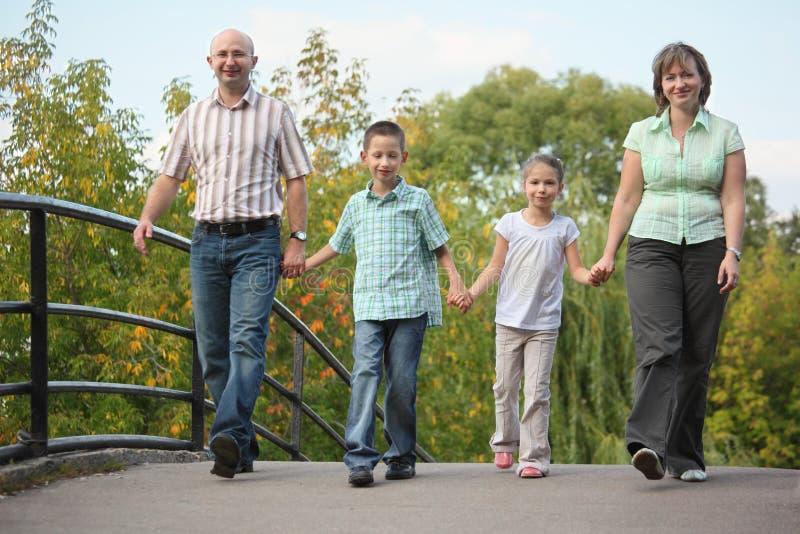 A família com duas crianças está andando na ponte fotos de stock royalty free
