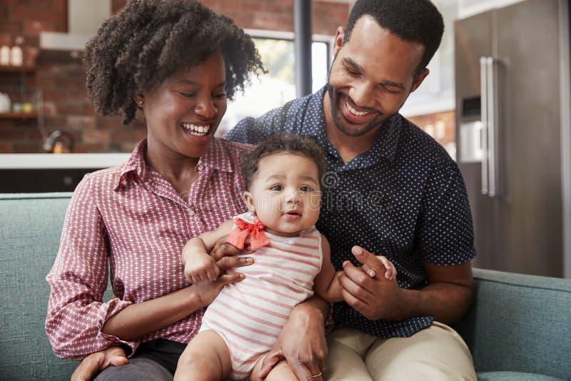 Família com a filha do bebê que relaxa em Sofa At Home Together foto de stock