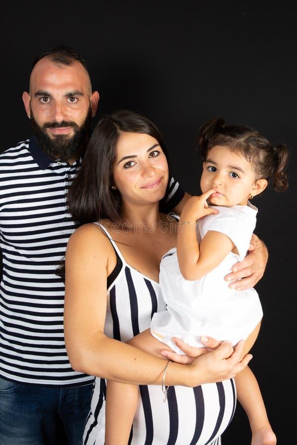 Família com a filha grávida do pai da mãe sob o fundo preto imagens de stock royalty free