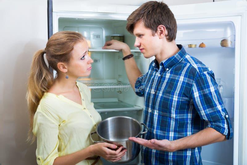 Família com fome que está perto do refrigerador vazio foto de stock