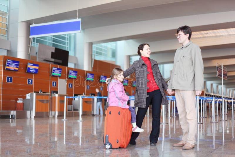 Família com a mala de viagem que está no salão do aeroporto imagem de stock royalty free