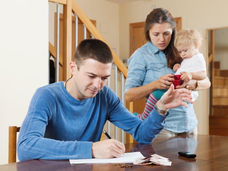 Família com o bebê que tem a discussão da discussão sobre o dinheiro imagem de stock
