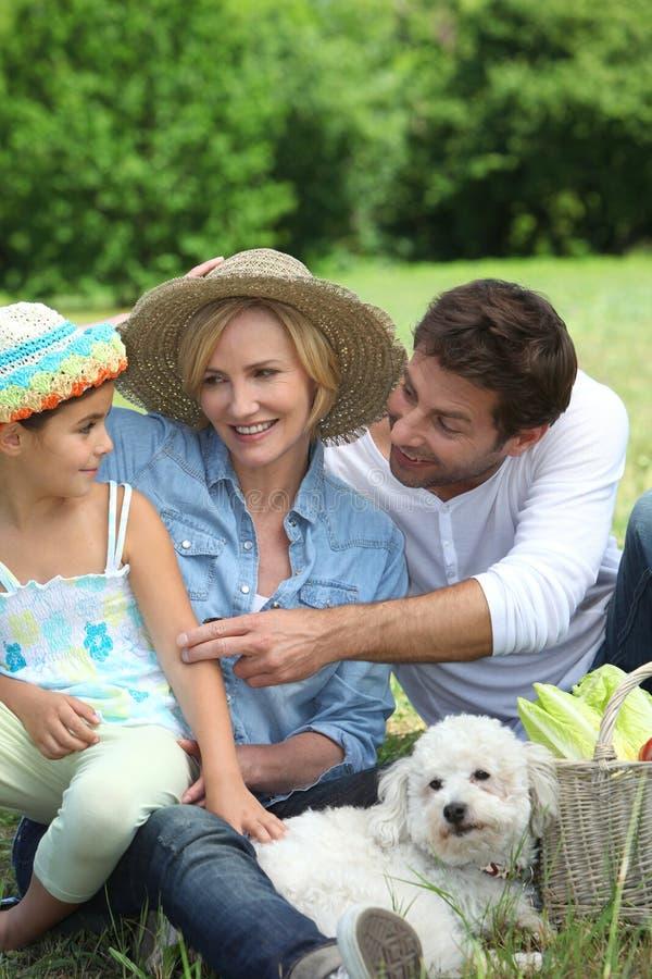 Família com o cão branco pequeno foto de stock