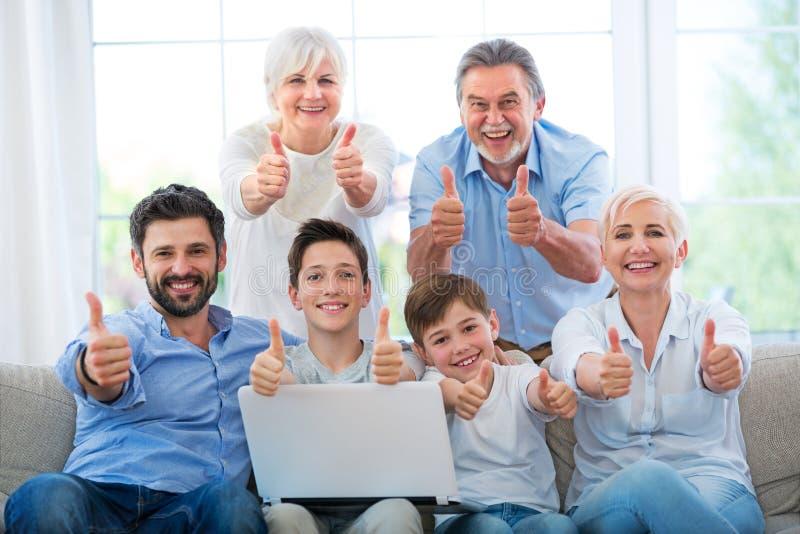 Família com o portátil que mostra os polegares acima imagens de stock royalty free