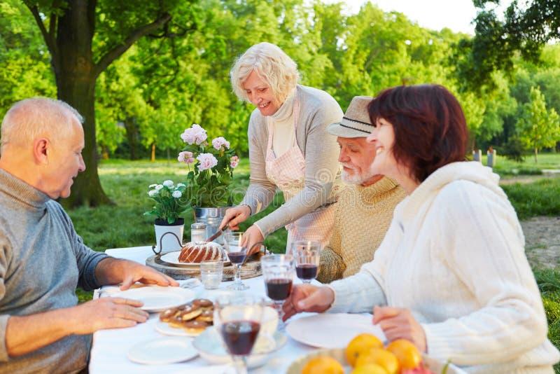 Família com os povos superiores que comem o bolo na festa de anos foto de stock royalty free