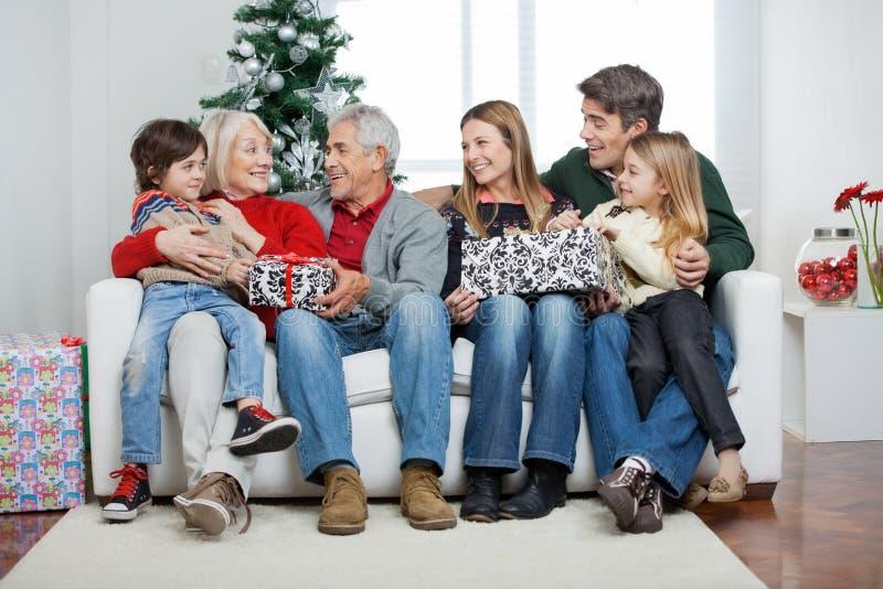 Família com os presentes de Natal que sentam-se no sofá fotos de stock royalty free
