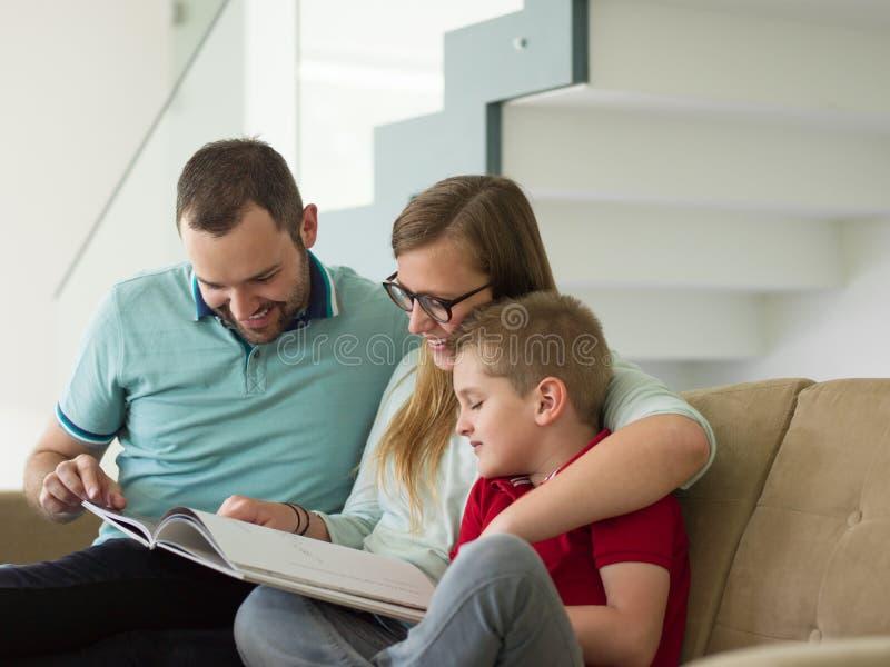 A família com rapaz pequeno aprecia na sala de visitas moderna imagem de stock royalty free