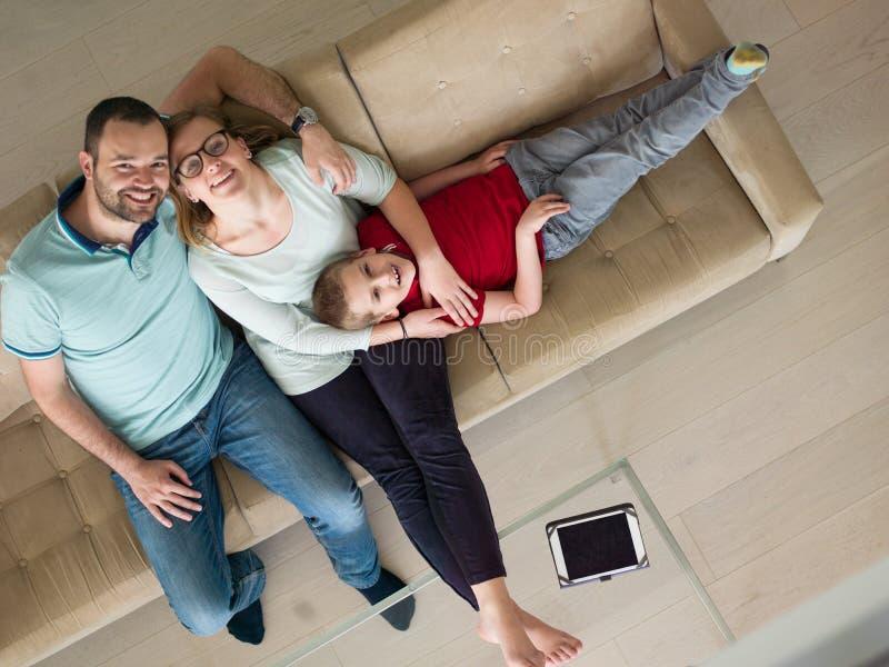 A família com rapaz pequeno aprecia na sala de visitas moderna fotografia de stock