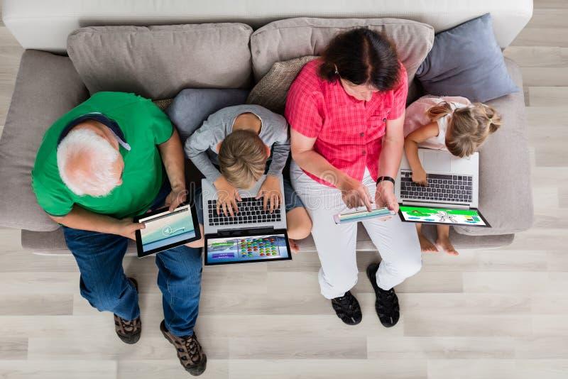 Família com seus portátil e tabuleta de Digitas em casa imagens de stock royalty free