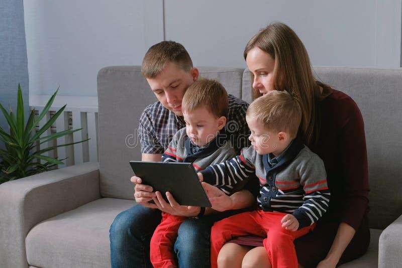 Família com tabuleta Mamã, paizinho e dois gêmeos dos filhos jogando jogos na tabuleta que senta-se no sofá fotos de stock