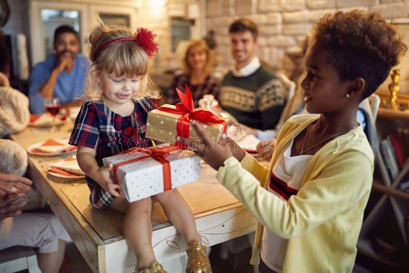 A família comemora o Natal - meninas alegres que recebem o presente do Natal da família fotografia de stock royalty free