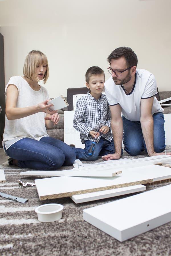 A família composta da mamã, do paizinho e do menino gerencie a mobília no tapete que tem o divertimento imagens de stock