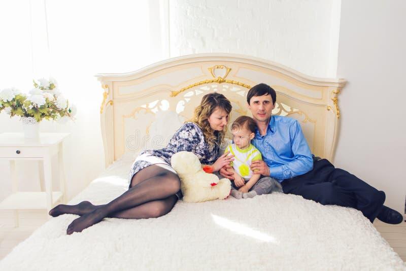 Família, conceito da paternidade e das crianças - mãe feliz, pai e filho que jogam junto com o urso de peluche na cama dentro foto de stock