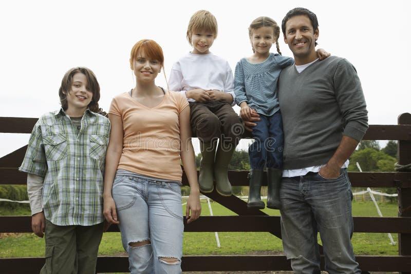 Família contra a cerca In Field imagem de stock royalty free