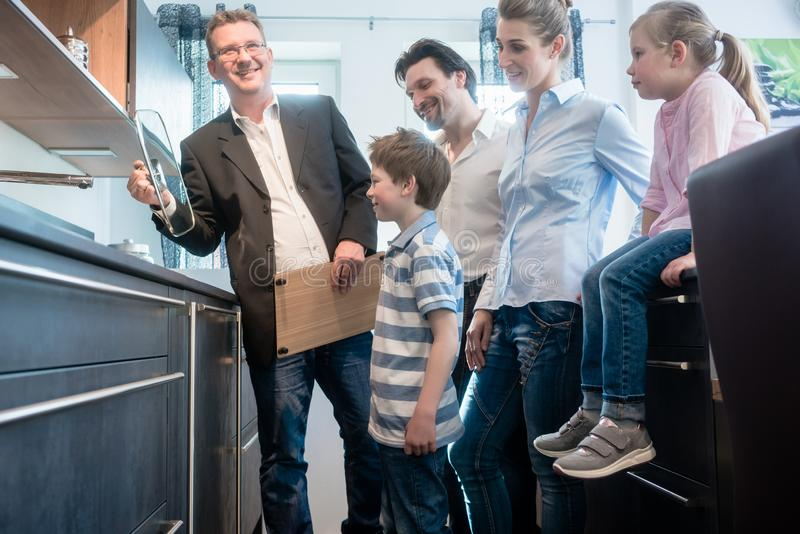 Família da exibição do vendedor as características de uma cozinha nova fotos de stock