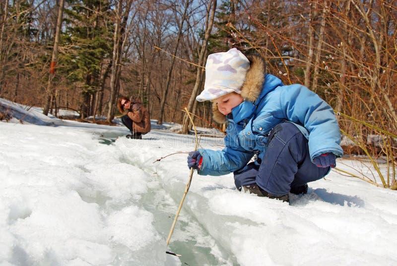 Família da mãe com a criança que joga na floresta da mola da neve fotos de stock