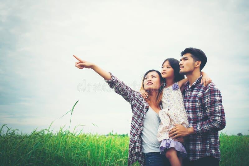 Família da mãe, do pai e da criança no prado, paizinho que leva o d imagem de stock