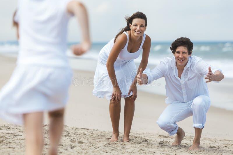 Família da mãe, do pai e da criança que corre tendo o divertimento na praia imagem de stock
