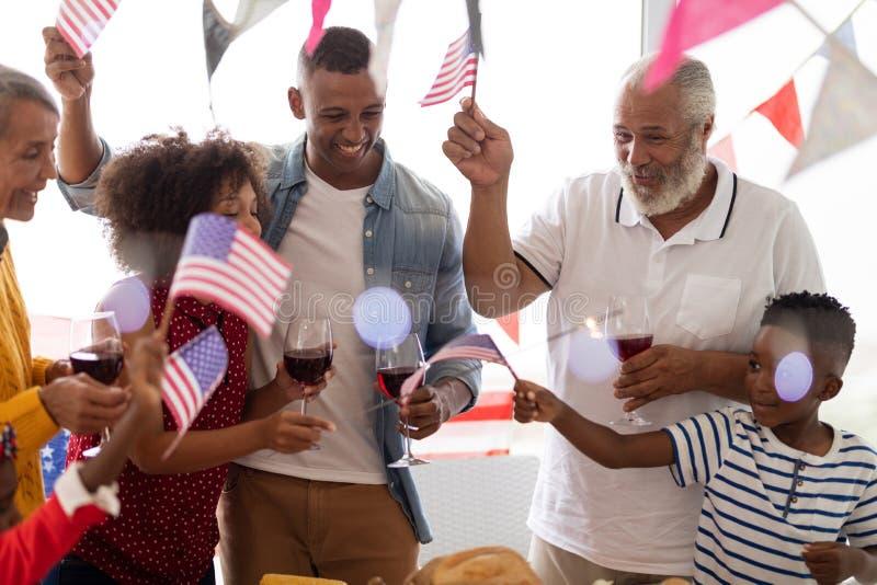família da Multi-geração que guarda a bandeira americana e que tem a celebração em uma mesa de jantar imagens de stock