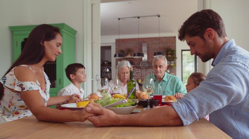 família da Multi-geração que reza antes de comer o alimento na mesa de jantar foto de stock