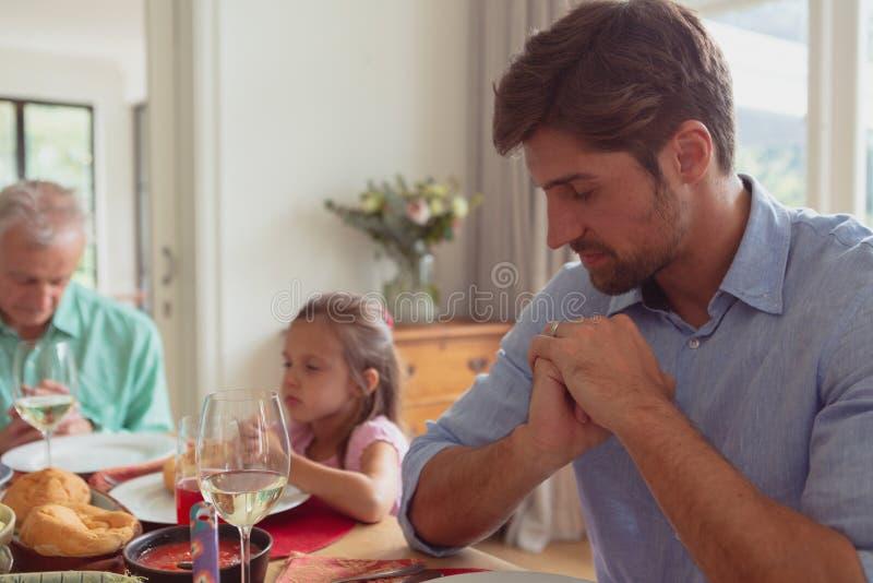 família da Multi-geração que reza antes de comer o alimento na mesa de jantar imagem de stock