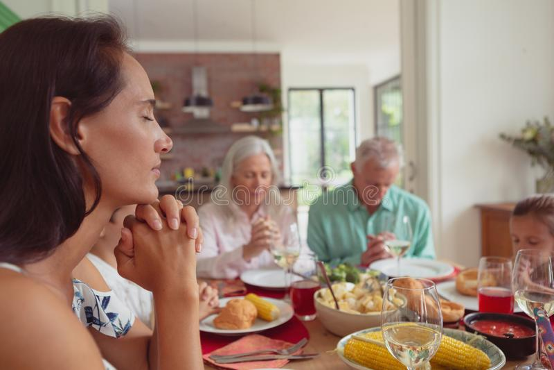 família da Multi-geração que reza antes de comer o alimento na mesa de jantar imagens de stock