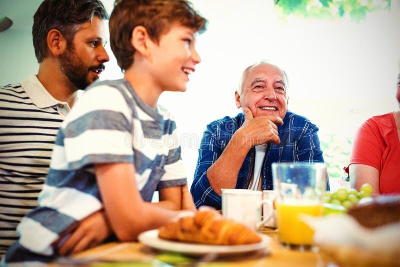 família da Multi-geração que senta-se na tabela de café da manhã fotos de stock royalty free